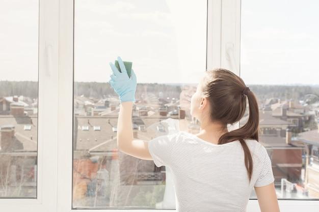 Vrouw reiniger in handschoenen in het appartement wast een raam met een spons