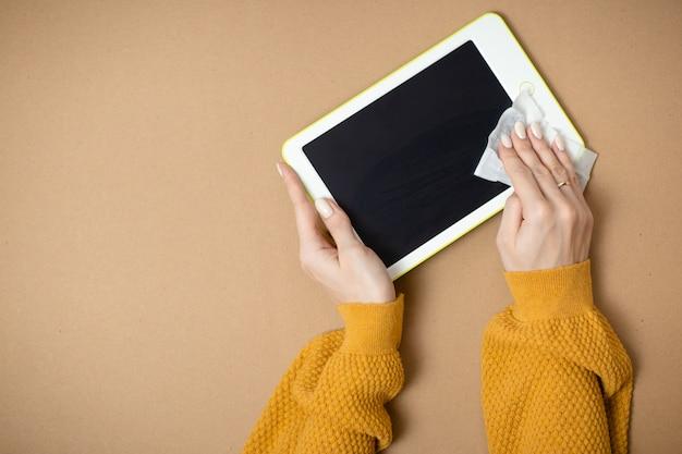 Vrouw reinigt witte tablet, gadget desinfectie terwijl virus. thuiskantoor terwijl u zelf isoleert, thuiswerkend. online onderwijs, e-learning tijdens quarantaine.