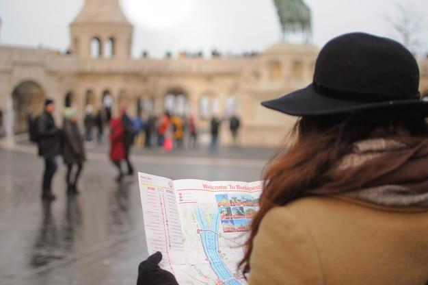 Vrouw reist alleen naar het buitenland in de winter meisje kijkt op de kaart om de weg te vinden