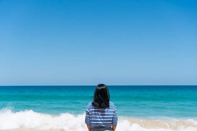 Vrouw reist de wereld rond met zomerse strandvrijheid en ontspannen leven