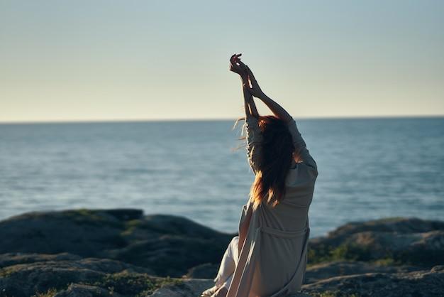 Vrouw reist in de bergen bij de zee en gebaart met haar handen boven haar hoofd in de