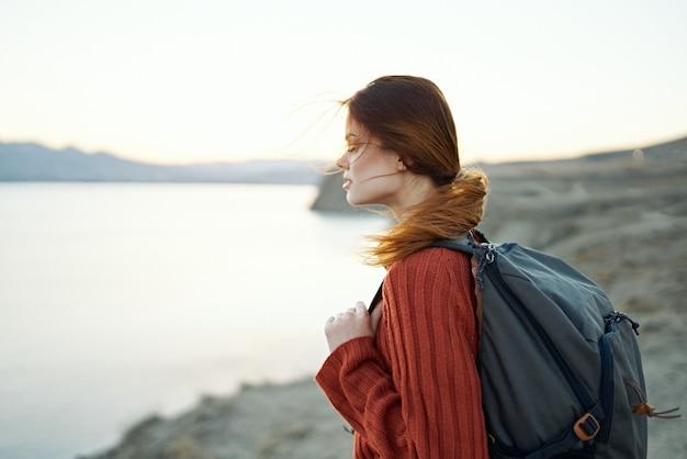 Vrouw reist in de bergen in de natuur in de buurt van het zijaanzicht van de zee