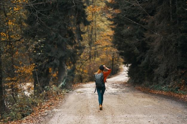 Vrouw reist in de herfstbos op het model van de rugzak van de hoge bomen van het weglandschap