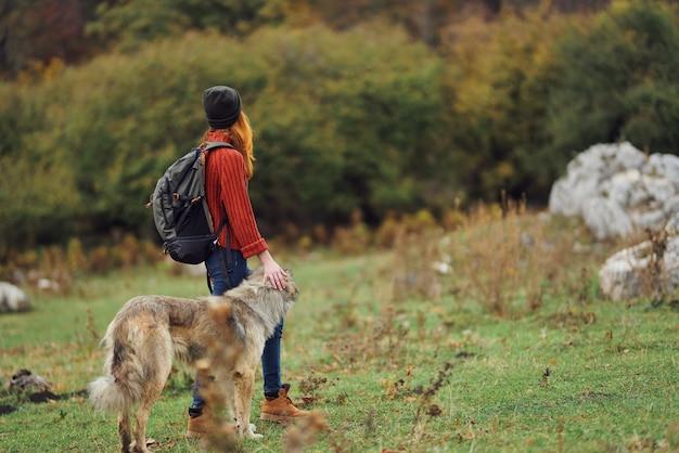 Vrouw reist in de natuur met een rugzak en hond