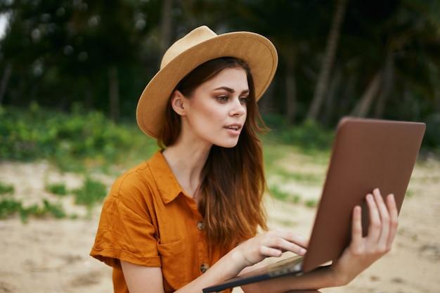 Vrouw reist met een laptop langs het zand met palmbomen
