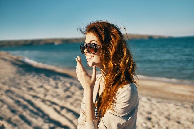 Vrouw reist op het strand in zonnebril in de bergen in de natuur