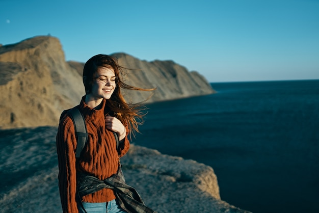 Vrouw reist over de natuur in de bergen met een rugzak in de buurt van de zee