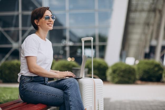 Vrouw reizen en werken op de computer op de luchthaven Premium Foto