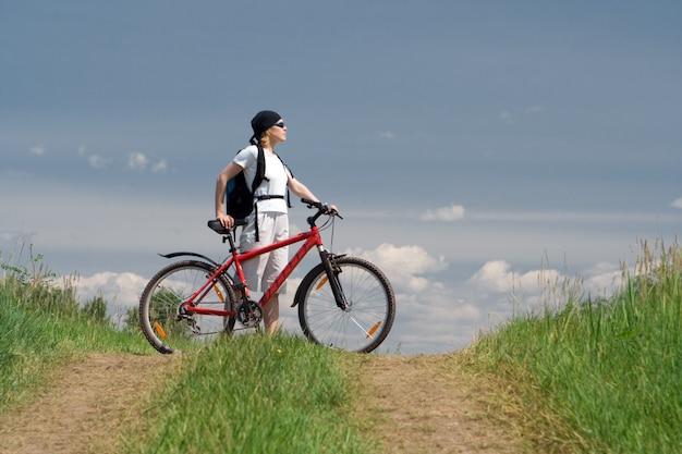 Vrouw reizen met fiets op weg in veld onder blauwe hemel met wolken