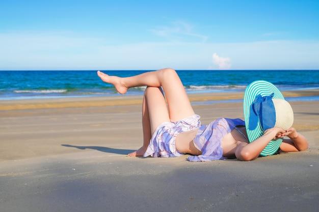 Vrouw reiziger in sexy zwembroek leugenachtig liggen op het strand