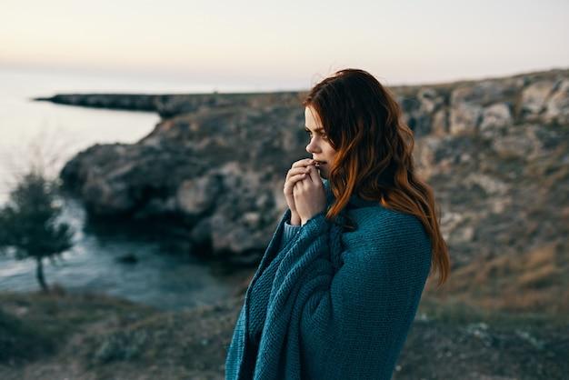 Vrouw reiziger met blauwe plaid in de bergen in de natuur