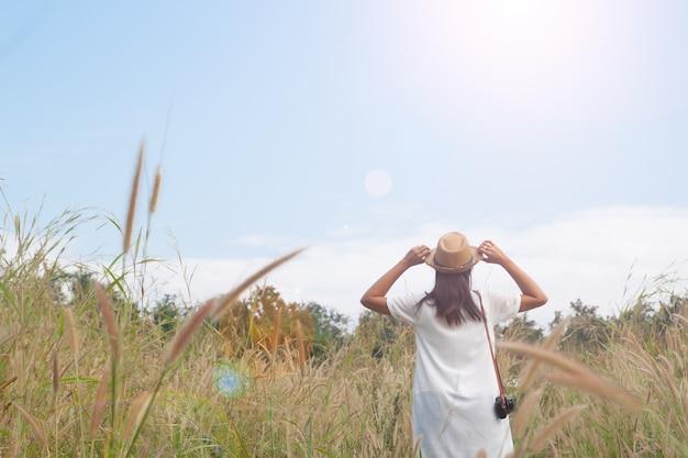 Vrouw reiziger met camera hoed en ademhaling in het veld van gras en bos, wanderlust reis concept, ruimte voor tekst, atmosferische epische moment