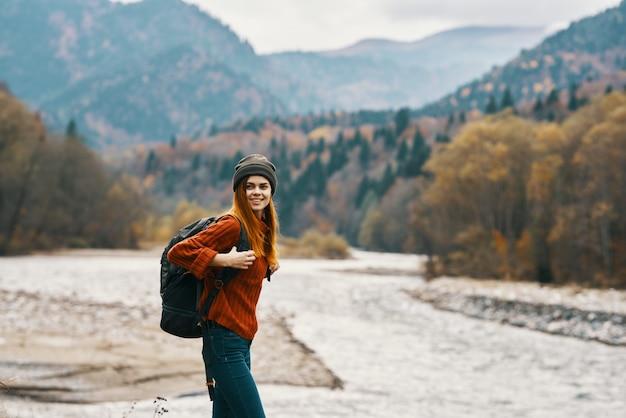 Vrouw reiziger met een rugzak in volle groei op de oever van de rivier in de bergen