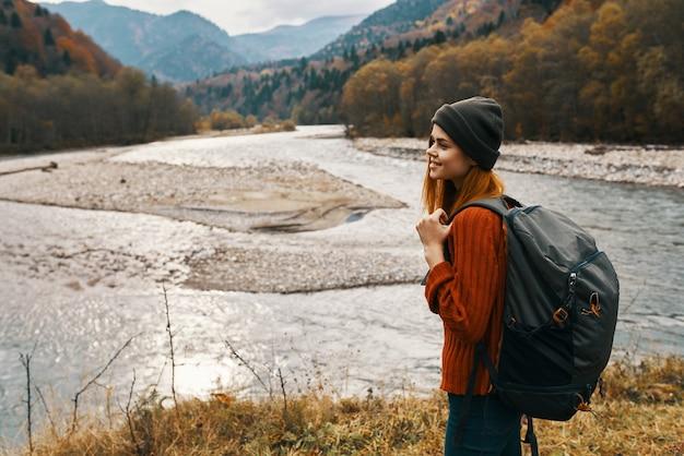 Vrouw reiziger met rugzak aan de rivieroever in de bergen