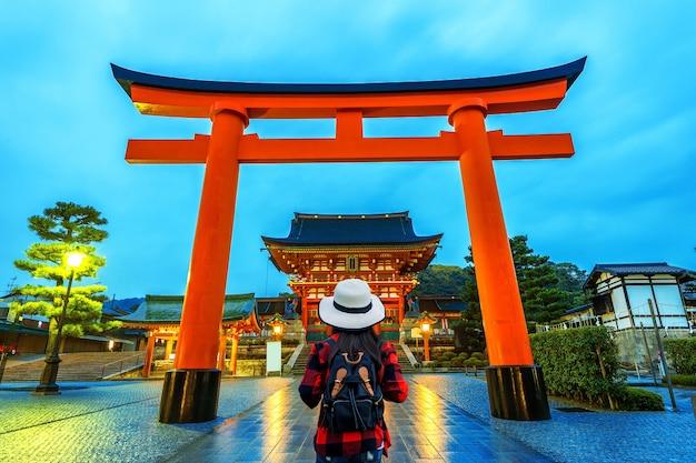 Vrouw reiziger met rugzak op fushimi inari taisha shrine in kyoto, japan.