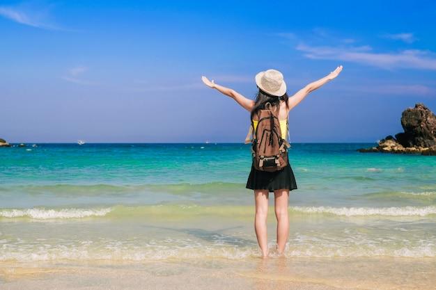Vrouw reiziger permanent en blij op het strand.