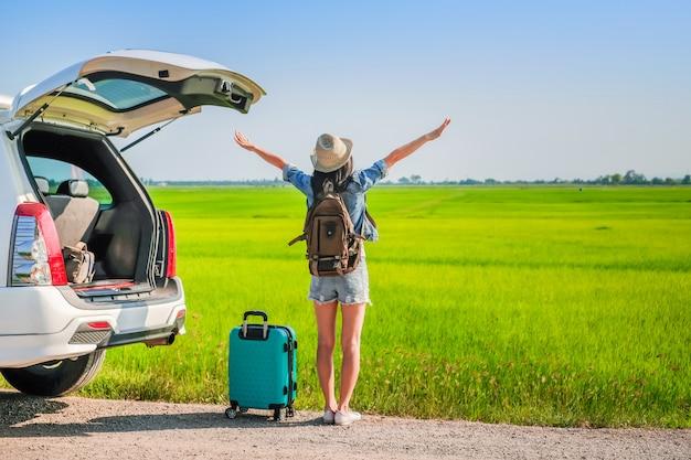 Vrouw reiziger permanent in de buurt van hatchback van de auto tijdens gaan reizen op vakantie