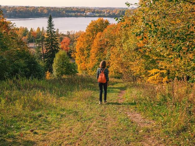 Vrouw reiziger wandelen met rugzak op herfst heuvel. reizen lifestyle concept avontuurlijke vakanties buiten.
