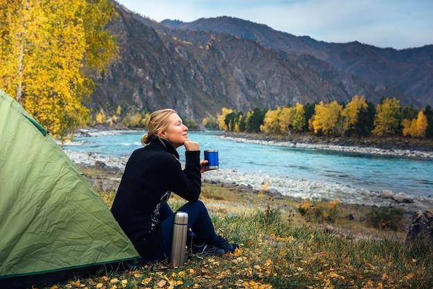 Vrouw reiziger zittend op gras in de buurt van de tent, koffie drinken uit thermosflessen en het prachtige uitzicht op de rivier en de bergen bewonderen. ochtend vrouw toerist, plezier in de reis.