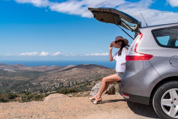 Vrouw reiziger zittend op hatchback auto met berg achtergrond