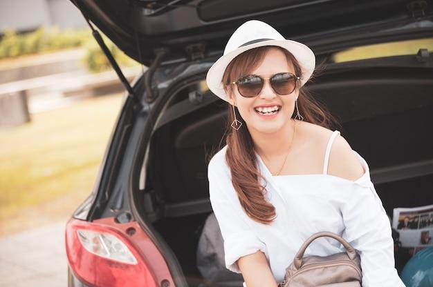 Vrouw reiziger zittend op hatchback auto