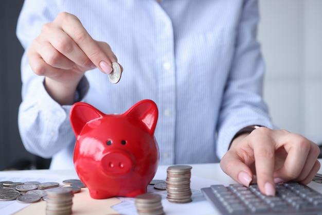 Vrouw rekenen op rekenmachine en munt aanbrengend spaarvarken close-up
