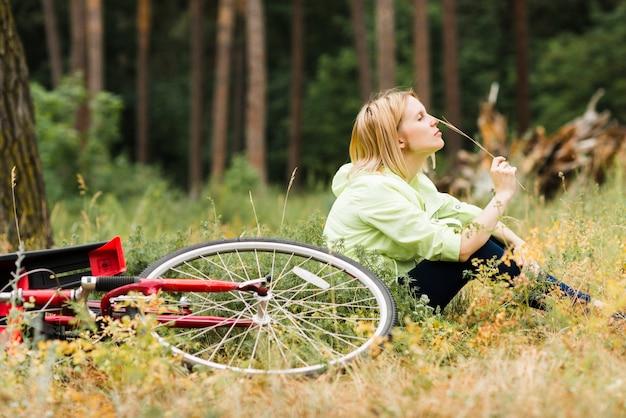 Vrouw relaxingnext aan fiets en weg het kijken
