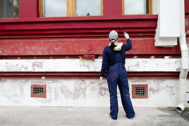 Vrouw, reparateur, timmerman, arbeider in beschermende kleding, schildert de muren van het gebouw. vrouwelijke handen in beschermende handschoenen met verfroller. het concept van professionele reparatie, restauratie.