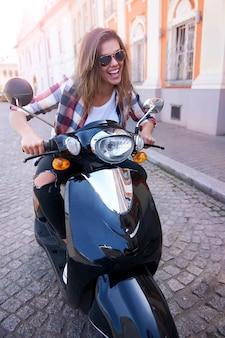 Vrouw rijdt op een motorfiets in de stad