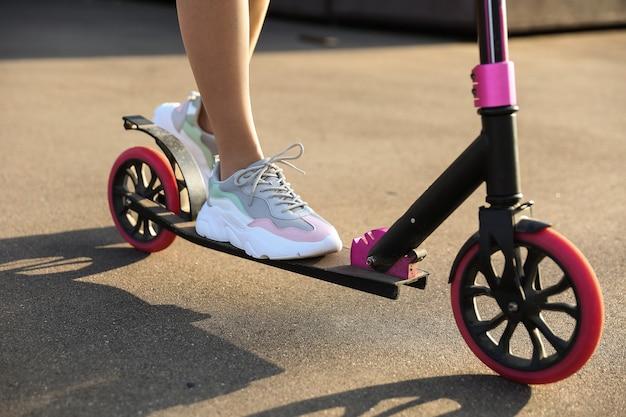 Vrouw rijdt op een scooter buitenshuis close-up