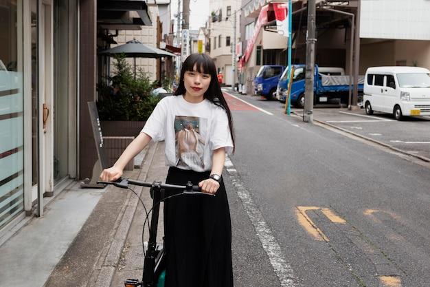 Vrouw rijdt op elektrische scooter in de stad