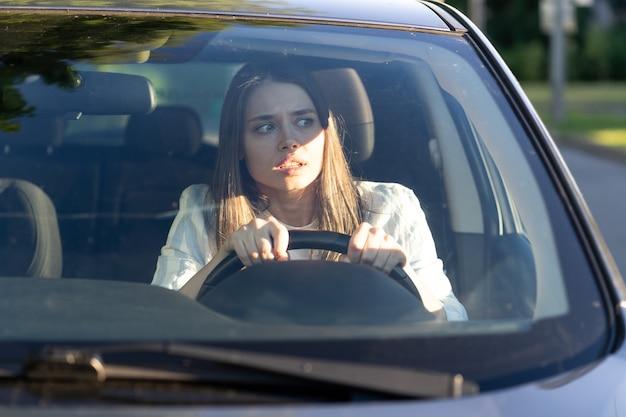Vrouw rijdt voor het eerst in haar auto, probeert een auto-ongeluk te vermijden, is erg nerveus en bang, maakt zich zorgen, klampt zich stevig aan het stuur vast. onervaren chauffeur in stress en verwarring na een ongeval