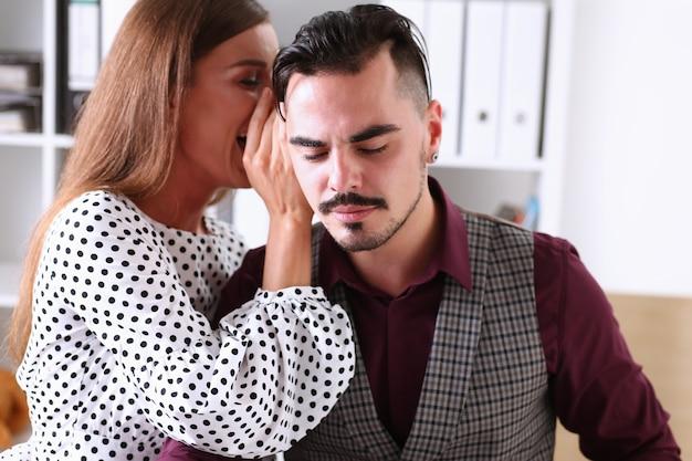 Vrouw roddel fluistert in het oor van nieuws aan een man