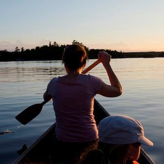 Vrouw roeien een boot met haar dochter, lake of the woods, ontario, canada