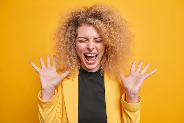 Vrouw roept blij uit, voelt zich opgewonden houdt handpalmen omhoog, gekleed in formele kledinghoudingen