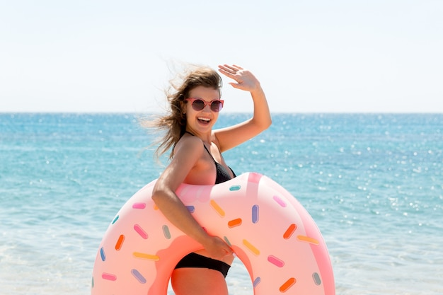 Vrouw roept om in de zee te zwemmen en zwaait met haar hand. meisje ontspannen op opblaasbare ring op het strand. zomervakantie en vakantie concept.
