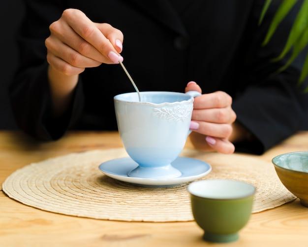 Vrouw roeren thee in mok met theelepel