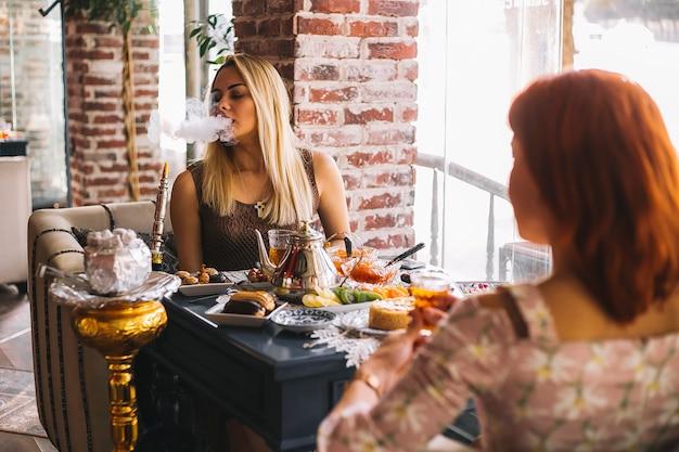 Vrouw roken shisha in het restaurant