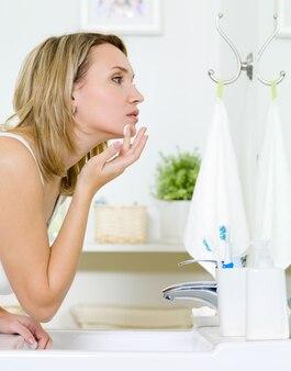 Vrouw room toe te passen op de wang - binnenshuis