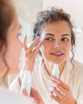 Vrouw room toe te passen op het gezicht tijdens het kijken in de spiegel