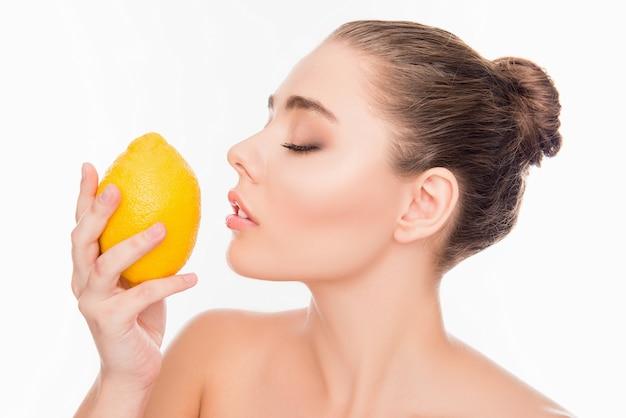 Vrouw ruikende citroen met gesloten ogen