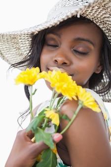 Vrouw ruikende gele bloemen