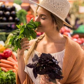 Vrouw ruikende natuurlijke bladeren op de markt