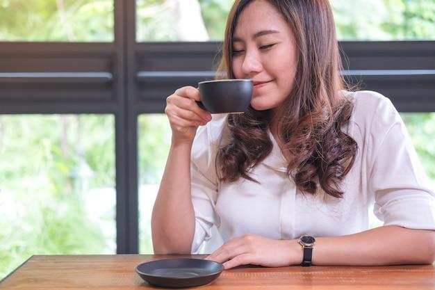 Vrouw ruikt en drinkt koffie