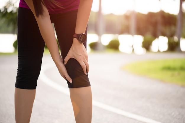 Vrouw runner voelt pijn op haar knie in het park.