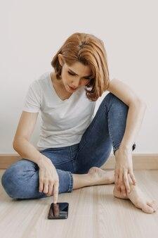 Vrouw rust en ontspant in de kamer met haar smartphone in de hand