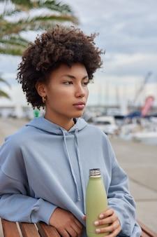 Vrouw rust na training heeft dorst heeft fles water vast gekleed in hoodie poseert buiten aan haven geniet van rust in vrije tijd
