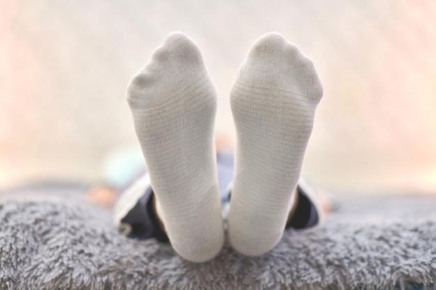 Vrouw rusten op de bank in gezellige zachte comfortabele sokken.
