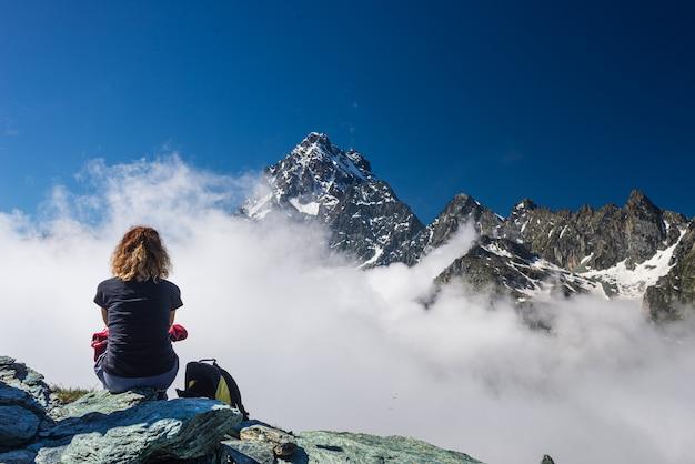 Vrouw rustend op de hoge bergtop, kijkend naar de majestueuze bergtop van het uitzicht dramatische landschap boven de wolken,