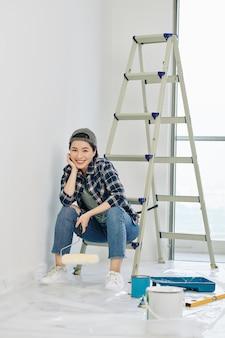 Vrouw rustend op de ladder na het schilderen